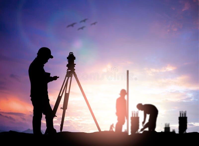 Siluetee al ingeniero de la encuesta que trabaja en un solar sobre la falta de definición imagen de archivo libre de regalías