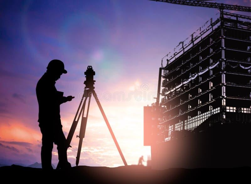Siluetee al ingeniero de la encuesta que trabaja en un solar sobre la falta de definición imágenes de archivo libres de regalías