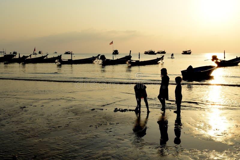 Siluetee al niño plaing en la isla Tailandia de tao del kho de la playa de la puesta del sol foto de archivo