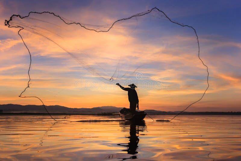 Siluetee al pescador en red del ajuste del barco de pesca con salida del sol fotos de archivo