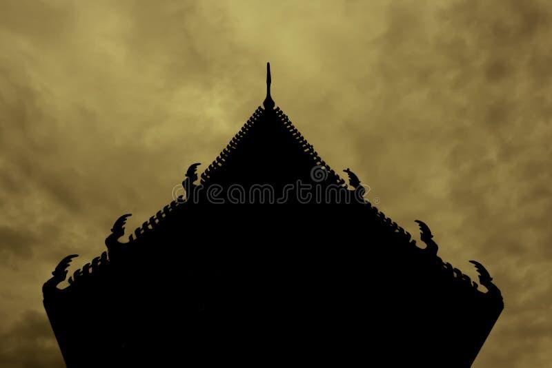 Siluetee del tejado la iglesia tailandesa del templo y hay un contexto del cielo anaranjado fotografía de archivo