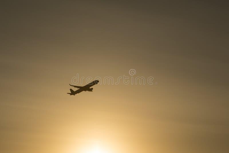 Siluetee el avión del despegue del aeropuerto mientras que puesta del sol imagen de archivo libre de regalías