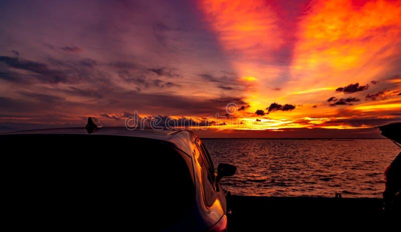 Siluetee el coche de SUV con deporte y diseño moderno parqueado en el camino concreto por el mar en la puesta del sol Viaje del v imagen de archivo