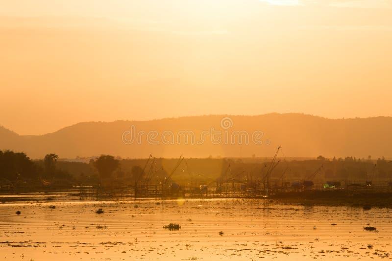 Siluetee el equipo de pesca en el tiempo de la salida del sol, presa de Huai Luang imagenes de archivo