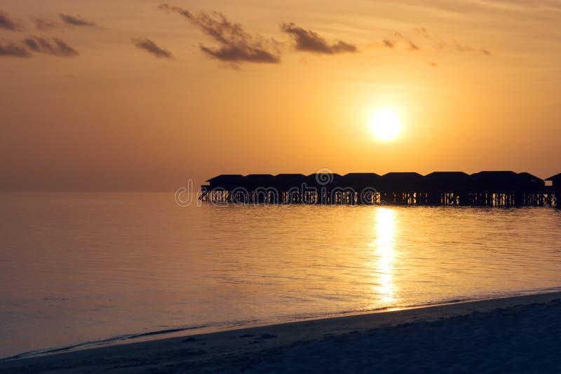 Siluetee el hotel turístico y la isla con la playa y el mar tropicales hermosos de Maldivas en el cielo de la puesta del sol para fotos de archivo