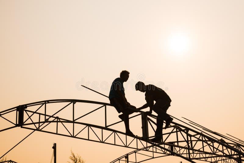Siluetee el trabajo en el tejado en la puesta del sol fotografía de archivo libre de regalías