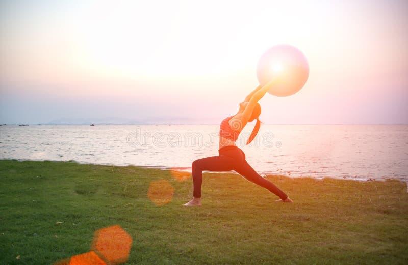 Siluetee la bola de la yoga y a la mujer joven de la bola de los pilates imágenes de archivo libres de regalías