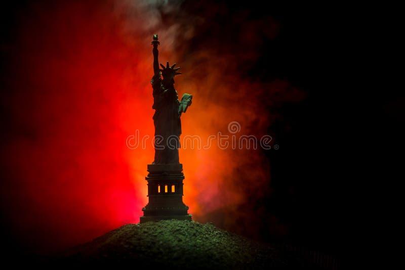 Siluetee la estatua de la libertad en fondo de niebla entonado oscuro Estatua de la libertad en el fondo del cielo colorido del a imagen de archivo libre de regalías
