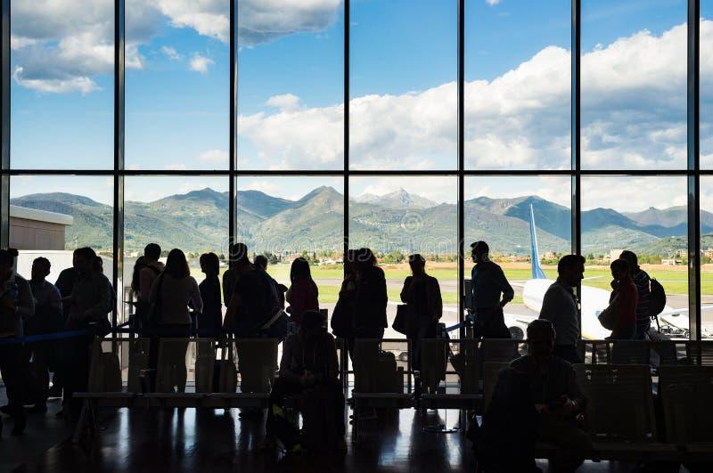 Siluetee a la gente de la cola que espera en la cola para el aeroplano en terminal con el fondo de la montaña foto de archivo libre de regalías