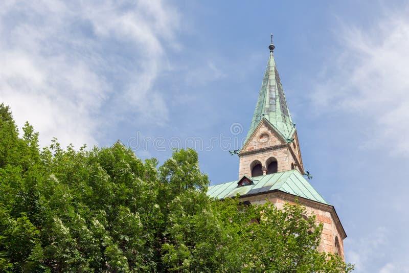 Siluetee la iglesia con la torre contra cuesta de montaña en Berchtesgaden, Alemania fotos de archivo