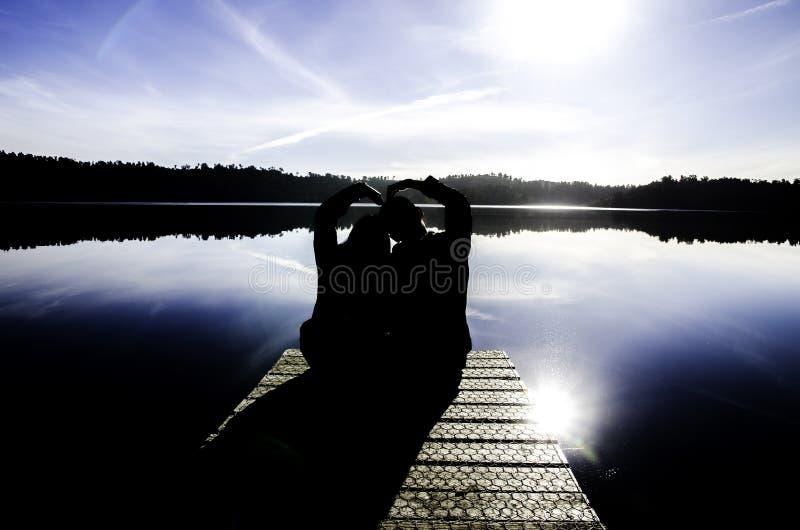 Siluetee la imagen de los pares que se sientan cerca del lago hermoso oscuro en la isla del sur, Nueva Zelanda imágenes de archivo libres de regalías