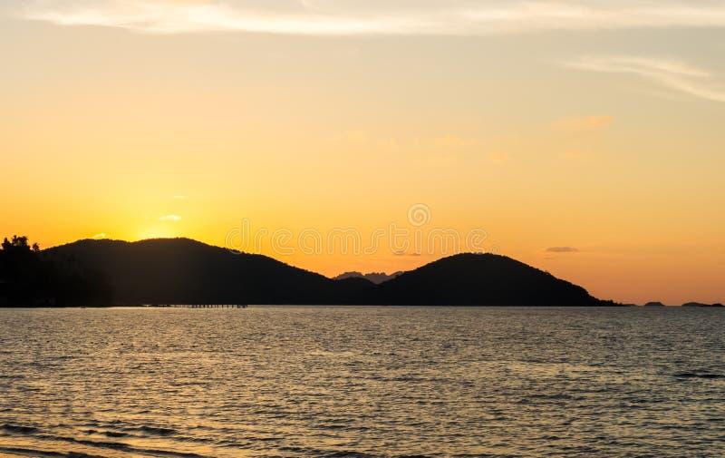 Siluetee la isla en el tiempo crepuscular, opinión tropical sobre la playa mientras que puesta del sol en Tailandia fotos de archivo