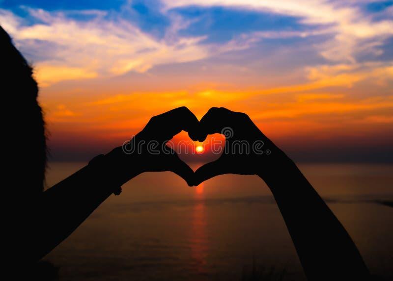 Siluetee la mano en forma del corazón con puesta del sol en el centro fotos de archivo libres de regalías