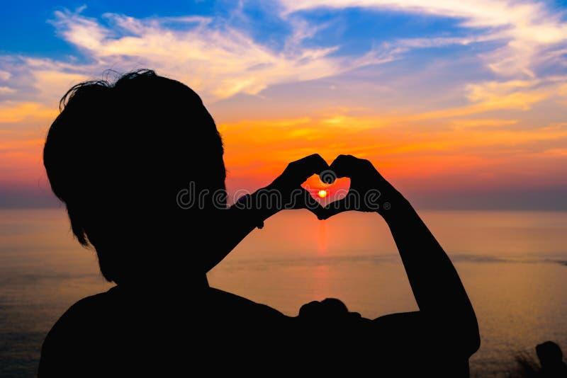 Siluetee la mano en forma del corazón con puesta del sol en el centro foto de archivo