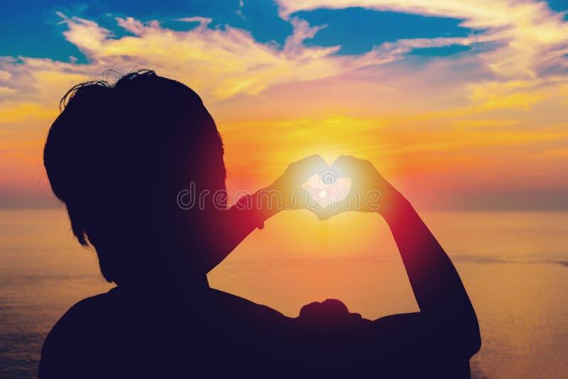 Siluetee la mano en forma del corazón con puesta del sol en el centro imagen de archivo libre de regalías