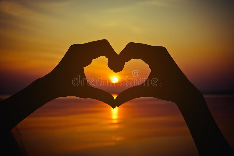 Siluetee la mano en forma del corazón con puesta del sol en el centro y el mar fotos de archivo