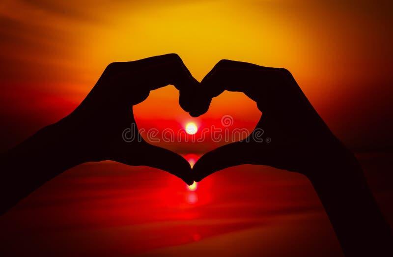 Siluetee la mano en forma del corazón con puesta del sol en el centro y el mar imagenes de archivo