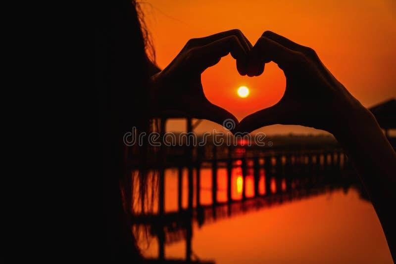 Siluetee la mano en forma del corazón con puesta del sol en el medio y azul fotos de archivo libres de regalías