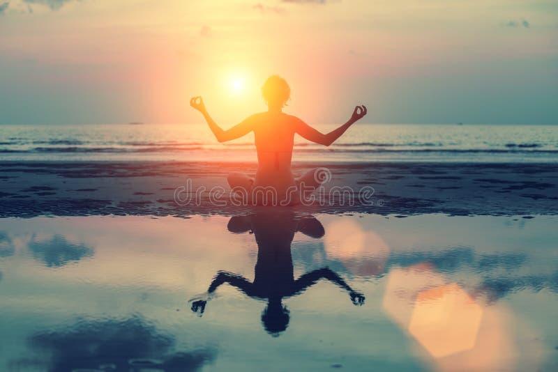 Siluetee a la muchacha de la meditación en el fondo del mar y de la puesta del sol imponentes imagenes de archivo