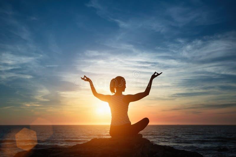 Siluetee a la muchacha de la meditaci?n en el fondo del mar y de la puesta del sol fotografía de archivo