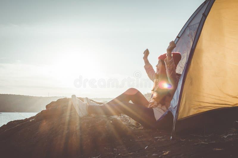 Siluetee a la mujer asiática que se relaja en la estación del invierno de la naturaleza durante acampar imagenes de archivo