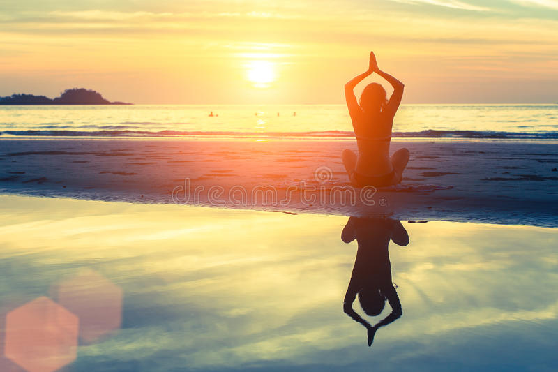 Siluetee a la mujer de la yoga de la meditación en el fondo del mar de la puesta del sol Naturaleza foto de archivo libre de regalías