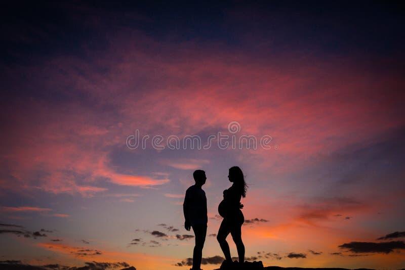 Siluetee a la mujer embarazada con su socio y puesta del sol foto de archivo libre de regalías