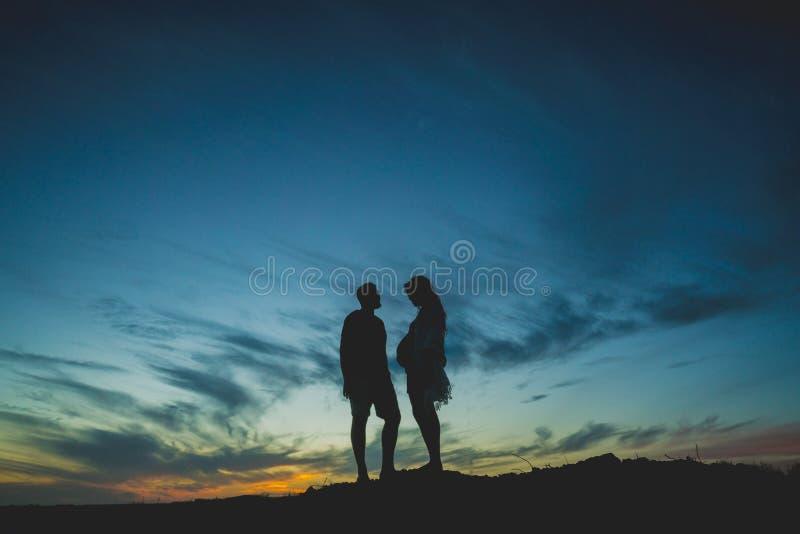 Siluetee a la mujer embarazada con su socio y puesta del sol imagen de archivo libre de regalías