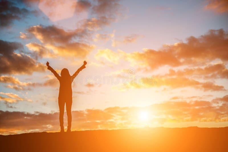 Siluetee a la mujer en la puesta del sol que se coloca regocijada con los brazos aumentó para arriba a fotos de archivo