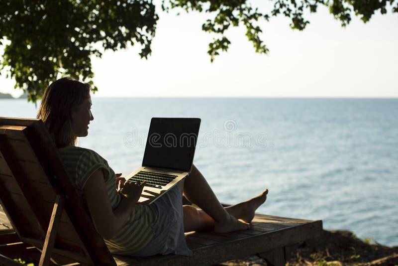 Download Siluetee A La Mujer En Un Ocioso Del Sol Con Un Ordenador Portátil En La Playa Foto de archivo - Imagen de pacífico, arena: 64206764