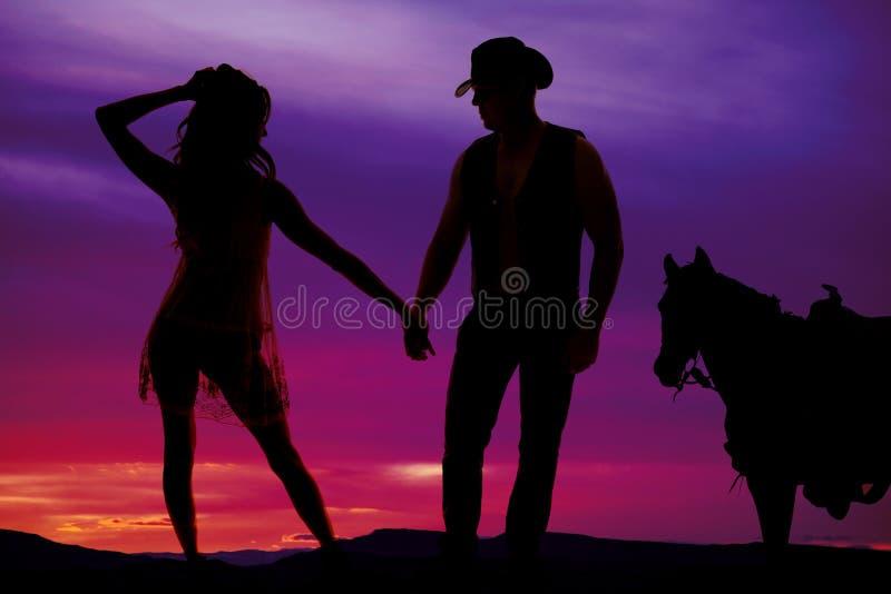 Siluetee a la mujer en vestido escarpado con el vaquero y el caballo foto de archivo