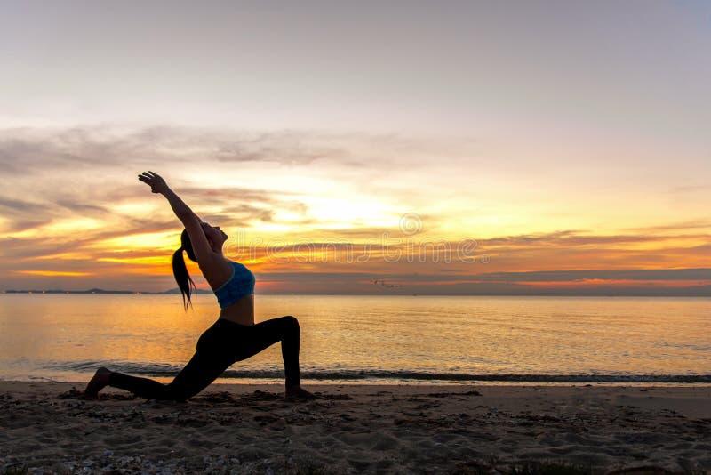 Siluetee a la mujer joven que el ejercicio de la forma de vida vital medita y bola practicante de la yoga en la playa foto de archivo