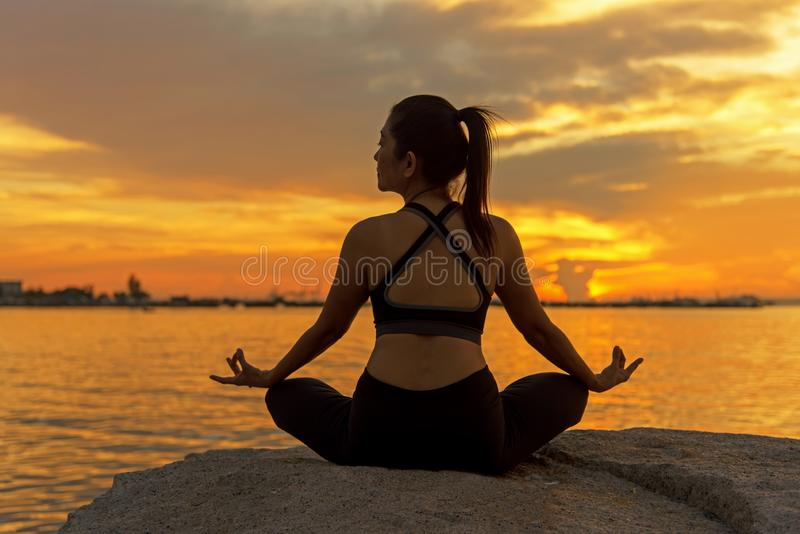 Siluetee a la mujer joven que el ejercicio de la forma de vida vital medita y bola practicante de la yoga en la playa en la puest imágenes de archivo libres de regalías