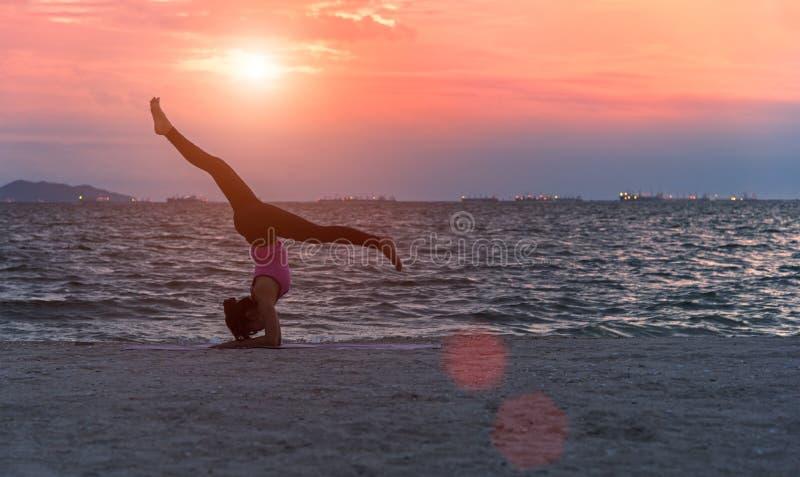 Siluetee a la mujer joven que el ejercicio de la forma de vida vital medita y yoga practicante en la playa en la puesta del sol foto de archivo libre de regalías