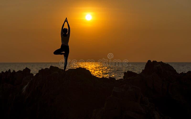 Siluetee a la mujer joven que el ejercicio de la forma de vida vital medita y yoga practicante en la playa en la puesta del sol fotos de archivo libres de regalías