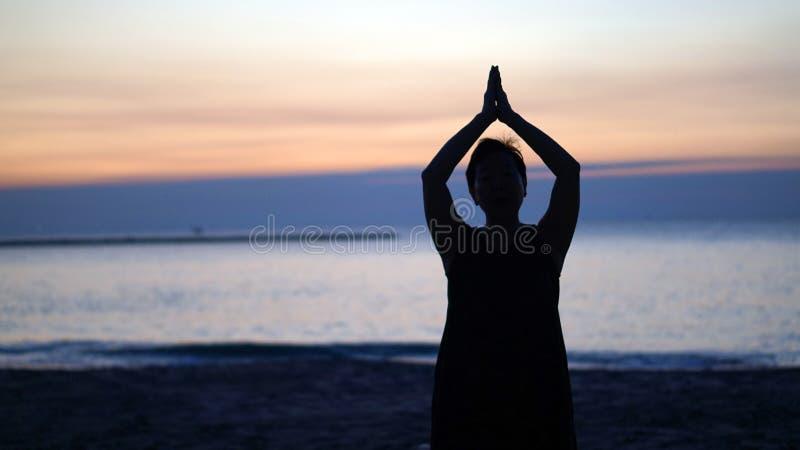 Siluetee a la mujer mayor asiática que hace yoga en la playa de la mañana foto de archivo