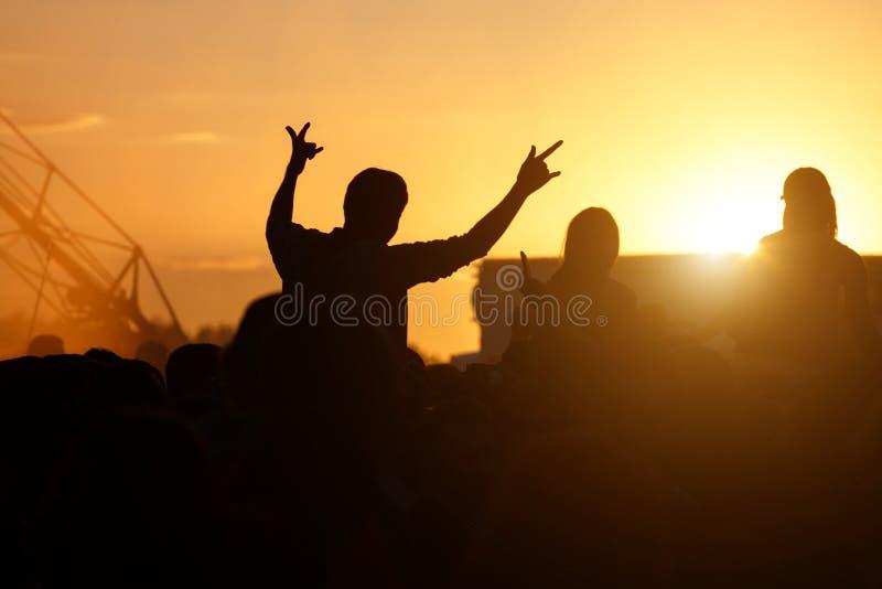 Siluetee a la persona del concierto, hombre en hombros en muchedumbre con las manos para arriba en el festival de música del vera imágenes de archivo libres de regalías