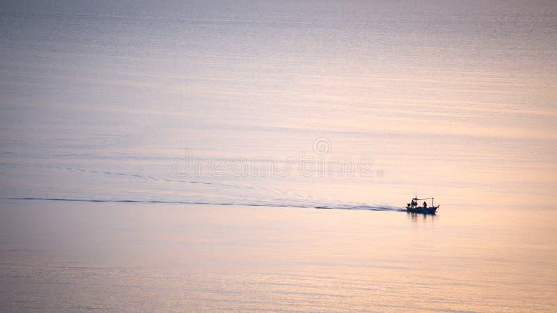 Siluetee la salida del sol de la vela mínima del barco de la industria pesquera en el mar tranquilo imagen de archivo
