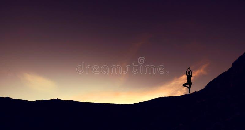 Siluetee la yoga practicante de la mujer joven del borde de la montaña en la montaña en salida del sol foto de archivo