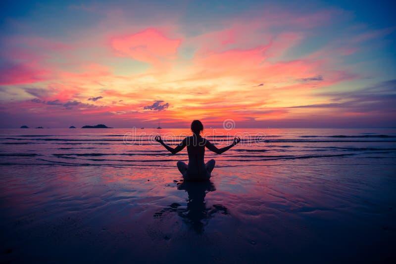 Siluetee la yoga practicante de la mujer joven en la playa en la puesta del sol Relájese imagen de archivo