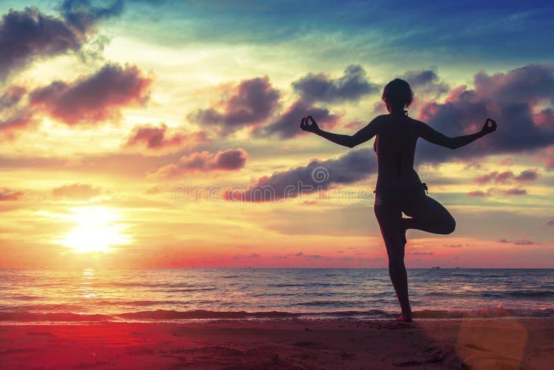 Siluetee la yoga practicante de la mujer joven en la playa en la puesta del sol surrealista fotos de archivo libres de regalías