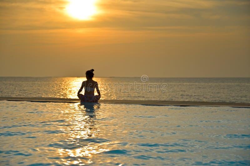 Siluetee la yoga practicante de la mujer joven en piscina imagenes de archivo