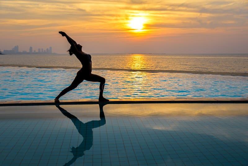 Siluetee la yoga practicante de la mujer joven en piscina y la playa en la puesta del sol fotos de archivo