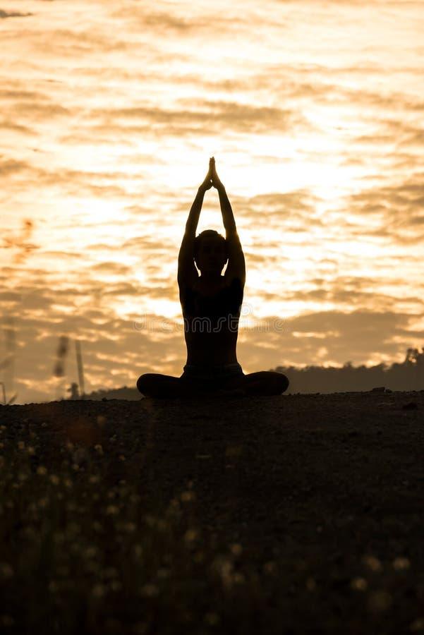Siluetee la yoga practicante de la mujer joven en la montaña en la puesta del sol imagen de archivo libre de regalías