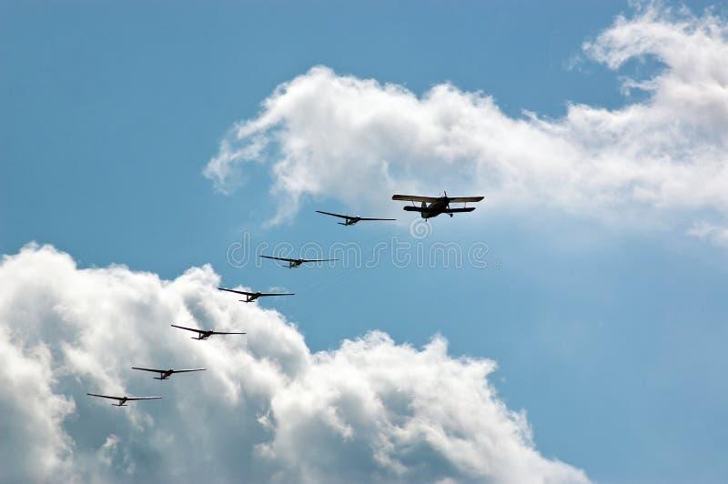 Siluetee los aviones del deporte con el propulsor y los planeadores, avión que tira de seis contra el cielo azul en el funcionami imagen de archivo libre de regalías