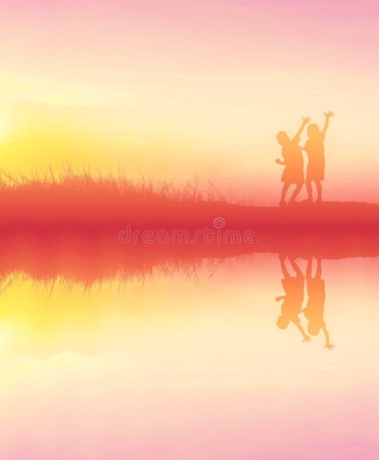 siluetee a los niños que juegan tiempo feliz en la puesta del sol con el refl del agua foto de archivo