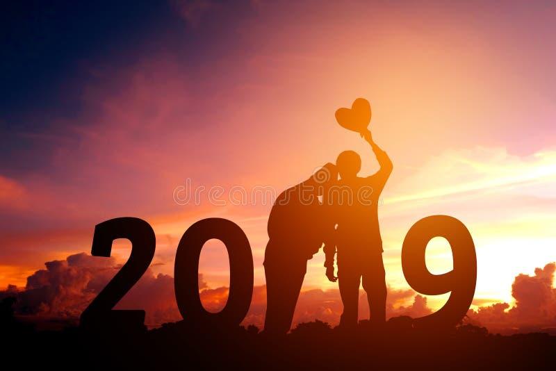 Siluetee los pares jovenes felices por 2019 Años Nuevos foto de archivo libre de regalías
