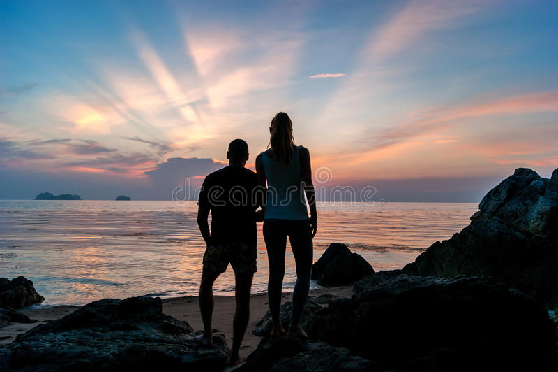 Siluetee los pares jovenes que se colocan en la playa que lleva a cabo las manos imagen de archivo libre de regalías
