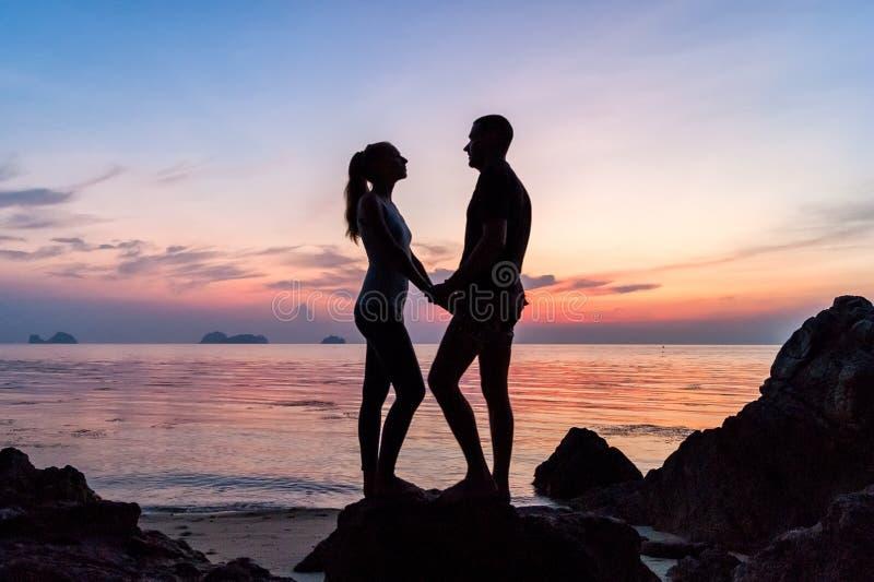 Siluetee los pares jovenes que se colocan en la playa que lleva a cabo las manos fotografía de archivo libre de regalías