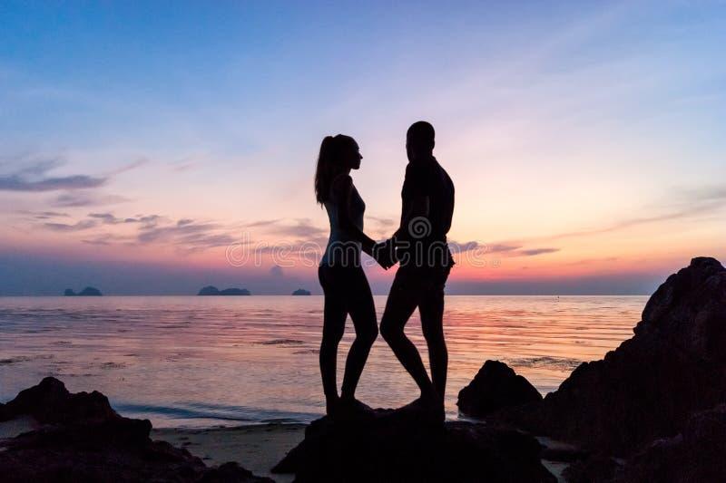 Siluetee los pares jovenes que se colocan en la playa que lleva a cabo las manos foto de archivo libre de regalías